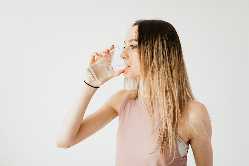 Femme qui boit de l'eau pour éliminer les toxines